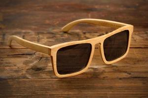 Bright wooden sunglasses on wooden surface