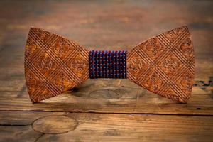 Wooden bow tie with fabric center on wooden background