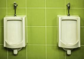 urinarios en una pared verde
