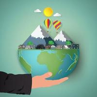Businessman's hand holding earth with mountains and houses vector
