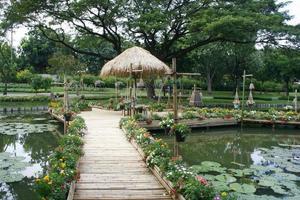 puente con una cabaña y flores en él foto