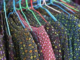 Coloridas camisas en perchas en una tienda.