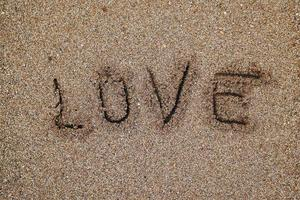 Love written on the sand in the beach