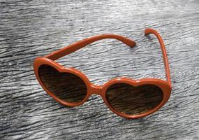 Heart-shaped sunglasses on wood