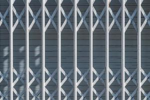 Rejas de seguridad blancas en una ventana urbana.