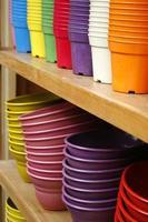 Colorful plastic flowers pots on shelves photo