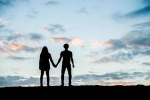 Silhouette of happy young couple together against beautiful sunset photo