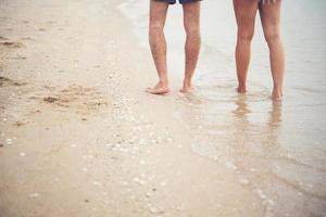 Rear of young couple walking on the beach with bare feet photo