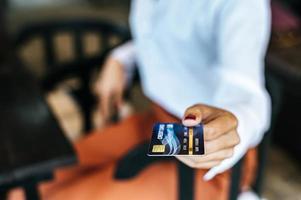 Mujer presentando tarjeta de crédito para pagar bienes. foto