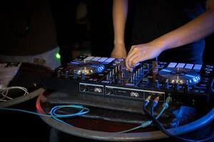 DJ playing turntable music at night club party photo