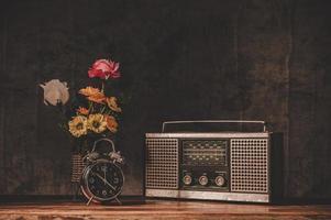 Retro radio receiver still life with clocks and flower vases