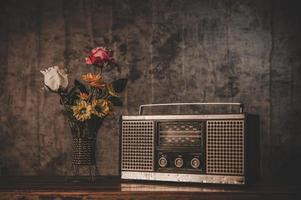Still life with a retro radio receiver and flower vases