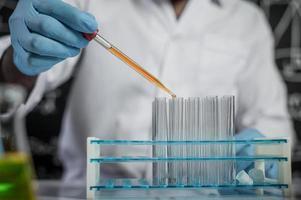 científico cae productos químicos de color naranja en vidrio en el laboratorio foto