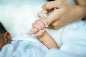 Newborn baby holding onto mom photo