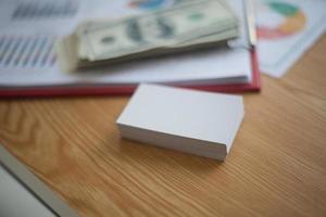 tarjetas de visita apiladas en el espacio de trabajo cerca de dinero en efectivo foto