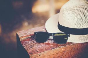 Hat and sunglasses on wooden bench at train station photo