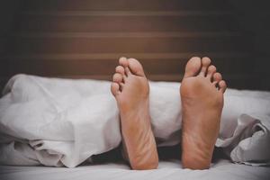 Man's feet under a blanket