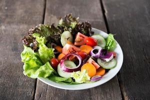 Ensalada de verduras frescas sobre fondo de madera foto