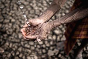 Elderly man shows open hands for water