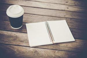 Blank notebook and cup of coffee on a wooden table photo