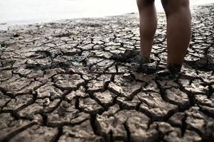 niño caminando descalzo sobre el barro foto