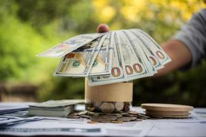 persona colocando efectivo en la mesa foto