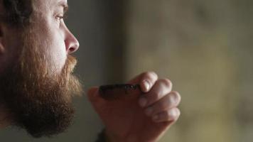 homem barbudo bebendo chá em uma tigela de barro