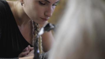 Retrato de chica tatuadora trenzada trabajando en un tatuaje