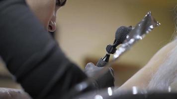 garota tatuadora com tranças trabalhando em uma tatuagem video