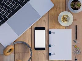 Vista superior del espacio de trabajo con café, pantalla de teléfono inteligente en blanco