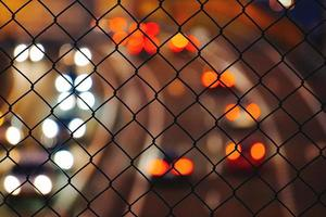 Fence with car lights bokeh