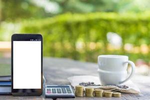 teléfono inteligente con pantalla en blanco y pilas de monedas foto