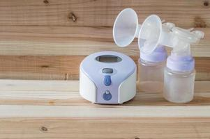 Electric breast pump to increase milk supply on wooden background photo