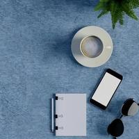 Mock up notebook and smart phone on blue table photo