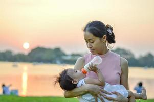 Portrait of mother and daughter in a summer park at sunset photo