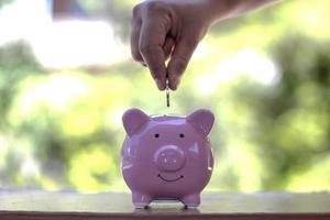 Close-up shot of a woman putting a coin in a piggy bank. Money saving concept