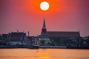 Bangkok, Thailand, 2020 - Bangkok temple under colorful sunset reflection on river
