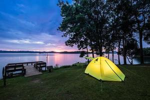 Tent near water at sunset photo