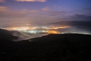 Foggy city lights and mountains