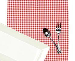 plato blanco con cubiertos sobre un paño rojo foto