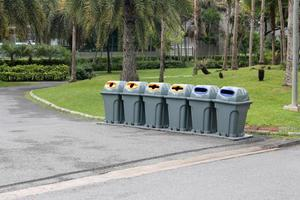 Row of trash cans in a park