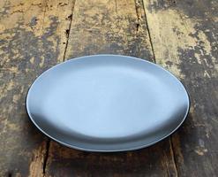 Round black plate on wood