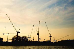 Construction cranes in Bangkok at sunset photo