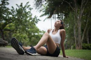 Young sporty woman sits at the park after a jog photo