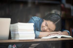 Portrait of hipster teenager sleeping at a cafe after reading a book photo