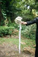 Cerca del novio con un hermoso ramo en las manos de la novia foto