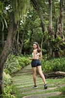 Rear view of sporty woman jogging at the park photo