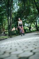 Young woman riding a bike in the park photo