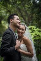 La novia y el novio de pie con el fondo verde del parque natural foto