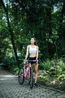 Portrait of a woman with a pink bike at the park photo
